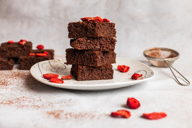 A small plate stacked with 4 brownies. Dried strawberries decorate it along with sprinkled cocoa.