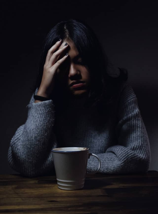 Depressed woman sitting in a dark room. Her hand rests on her forehead in obvious stress. A cup of coffee sits in from of her. She is wearing a sweater.
