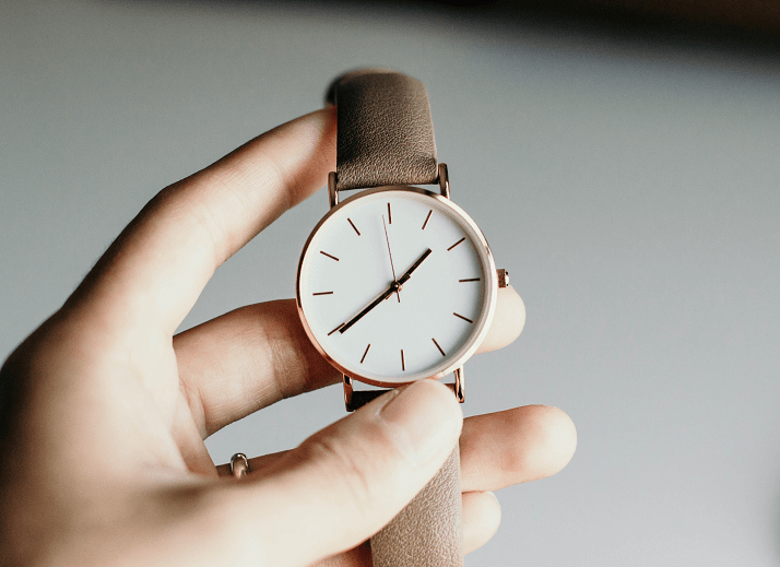 A person holding an analog watch.