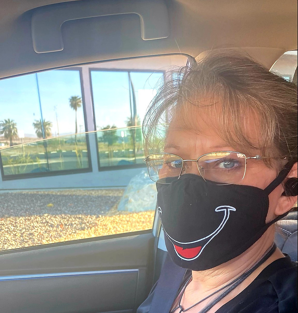 Photo of the authors head. She is wearing a black mask with a smiling face on it. She is in her car.