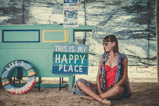 Women in red swimsuit sitting on the beach in the shade next to a sign that says This is my Happy Place.
