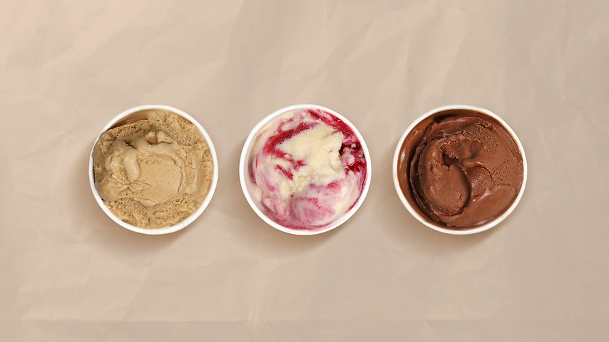 A variety of flavors of local ice cream for tasting and serving.