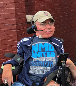 TK in his power wheelchair wearing an NMD United tee shirt in front of a red brick wall.