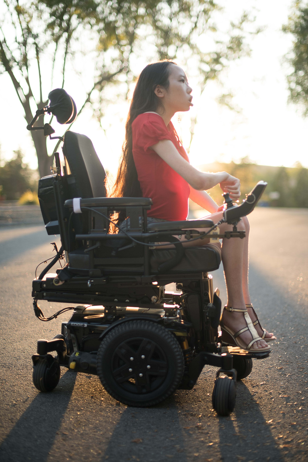 Right-side view of a Chinese American woman in a power wheelchair at sunset.