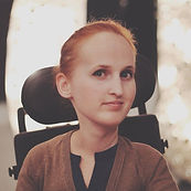 White woman with bright red hair pulled back. Wheelchair headrest is visible.