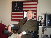 White man sits in a wheelchair wearing a suit. The ADAPT flag behind him.