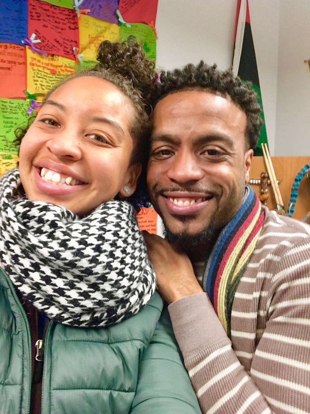 Two black people with short curly hair smile directly at the camera. Vic is wearing a green jacket and a black and white checkered scarf. Jadrien is wearing a brown and white striped long sleeve thermal shirt, and multicolored scarf. He is leaning against Vic.
