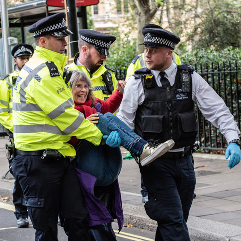 A climate activist is detained by police during the October 2019 Extinction Rebellion climate strike