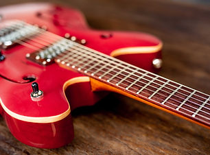 red-electric-guitar-on-wooden-floor.jpg