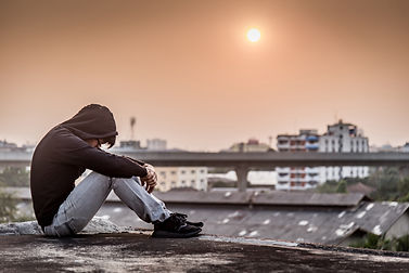 Canva - Young Asian man sitting on rooft