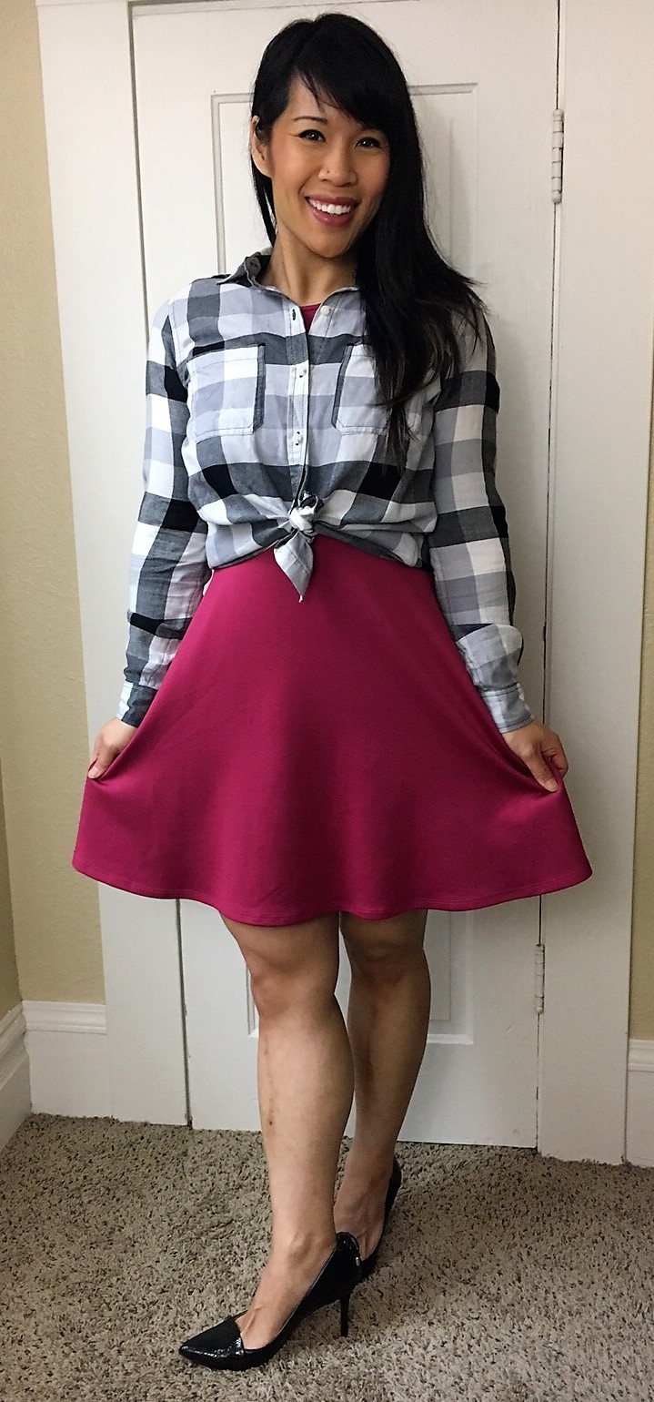 Kat wearing pink skater dress with tied flannel shirt