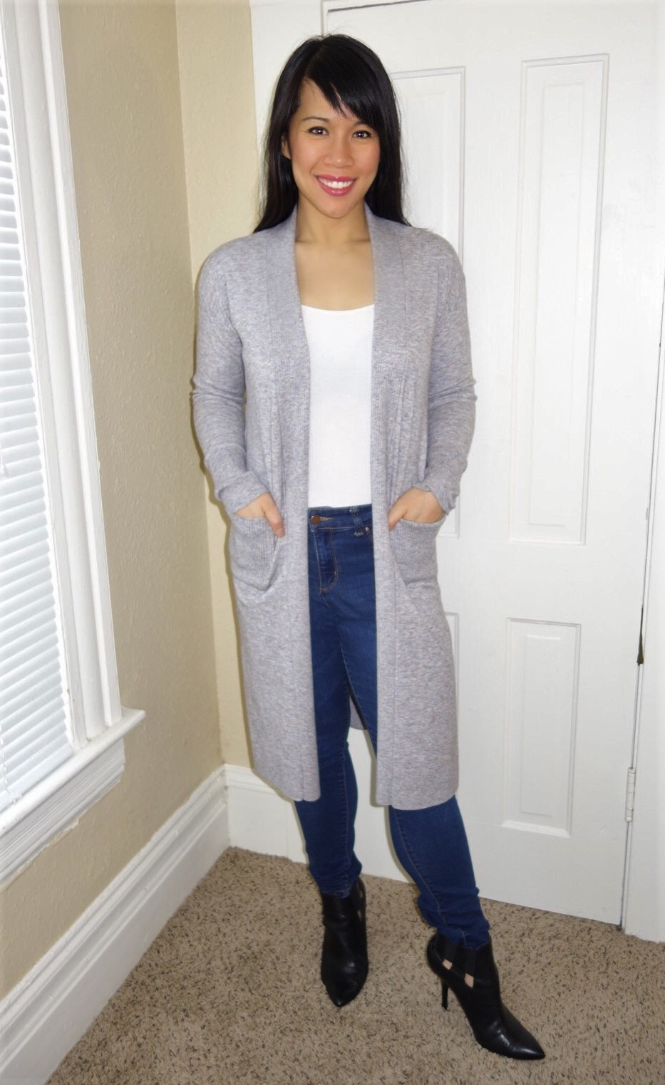 Kat wearing a grey duster, white tank, and blue jeans to illustrate minimalist style