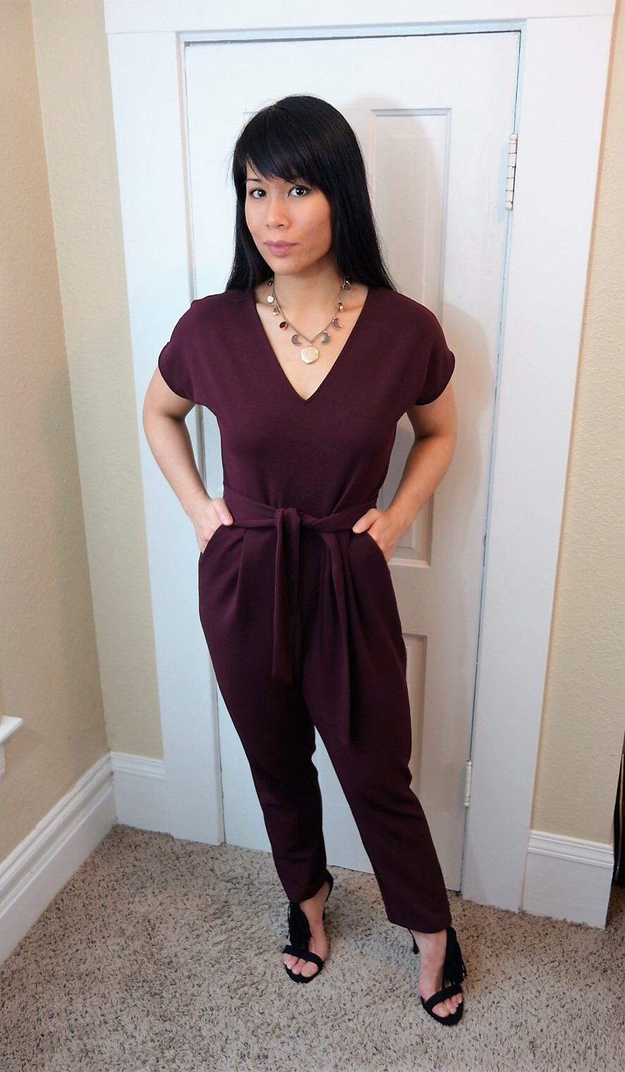 Kat Depner wearing a deep red jumpsuit for date night