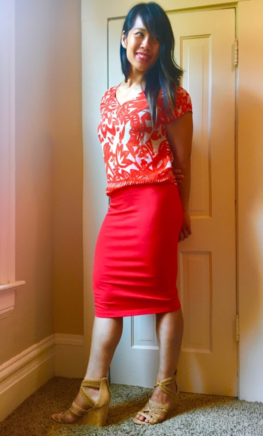 Kat posing in orange skirt with patterned orange top for a slimming effect