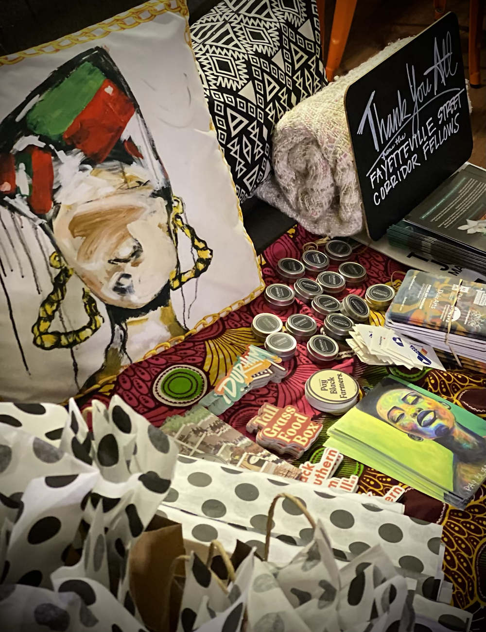 a grey couch holds African Ankara fabric, a black and white lumbar pillow, a white blanket, brown gift bags with black and white tissues, and contents of those bags. To the far left, a pillow cover of a Hip Hop Queen, designed by Rachel Stewart.