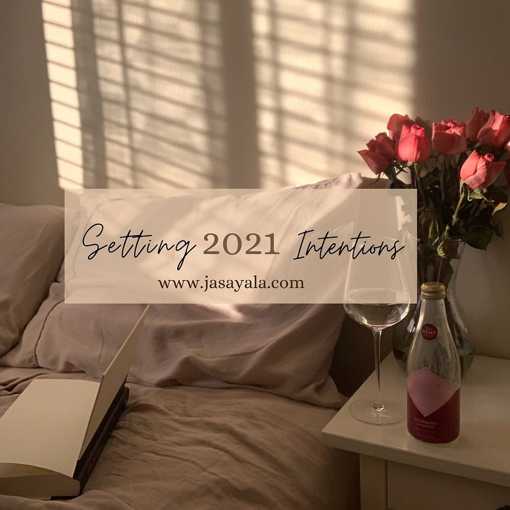 """Moody lighting peering through window onto bed with book open faced and a bouquet of pink roses on nightstand. Text overlay saying """"setting 2021 intentions"""" from jasayala.com"""