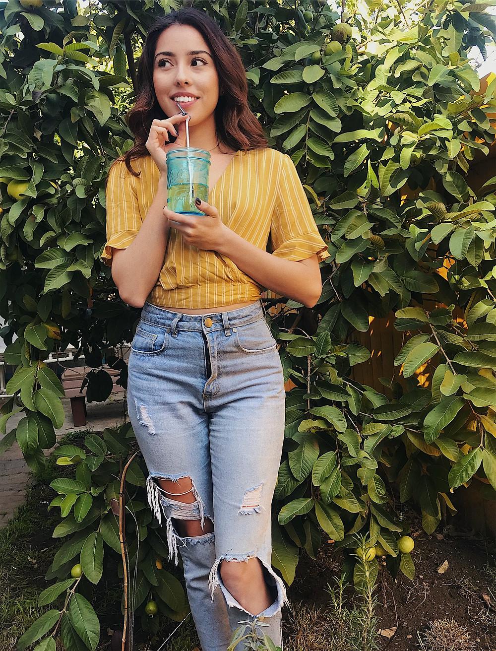 Girl Smiling holding resusable mason jar with metal straw eco friendly living sustainable zero waste lifestyle blog post 90's fashion