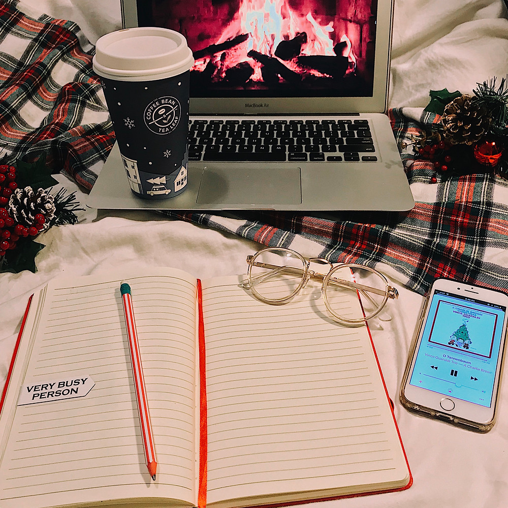 Seasonal Holiday christmas fireplace flatlay photo with charlie brown christmas playlist coffee bean and tea leaf latte with journal