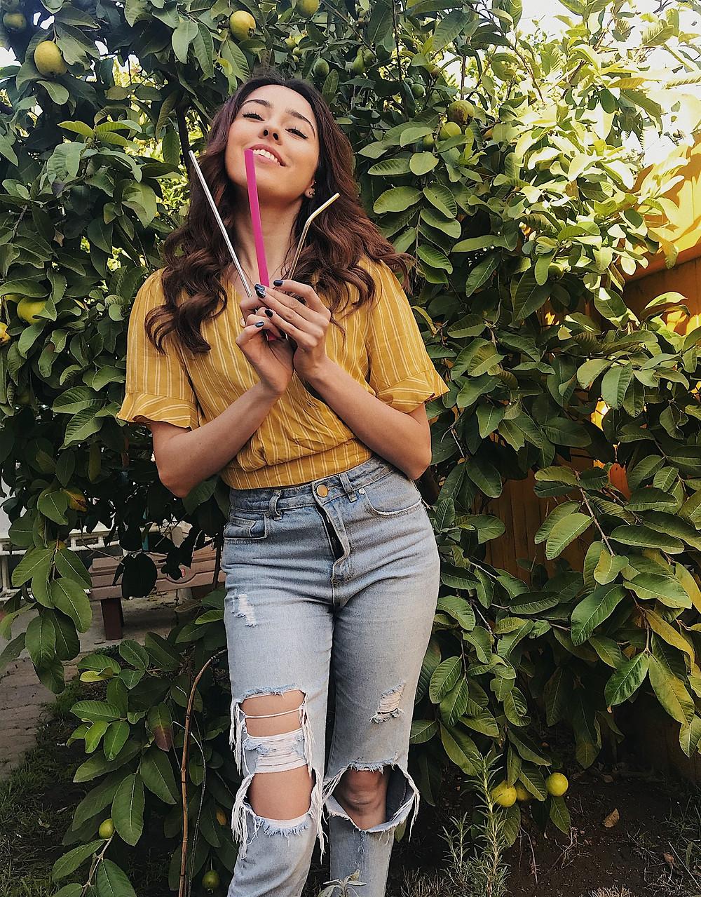 Girl smiling holding metal reusable silicone straws sustainable living zero waste lifestyle blog 90's fashion