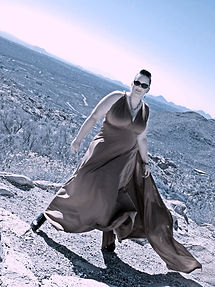 young woman in  gown sunglasses on mountain top in the wind