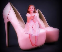 Little blond haired girl in pink dress playing peek a boo while sitting on oversized pink high heels