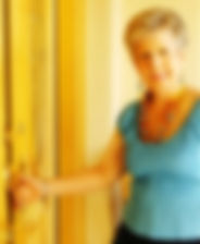 Mature blond woman in blue shirt and jewelry opening front door of home