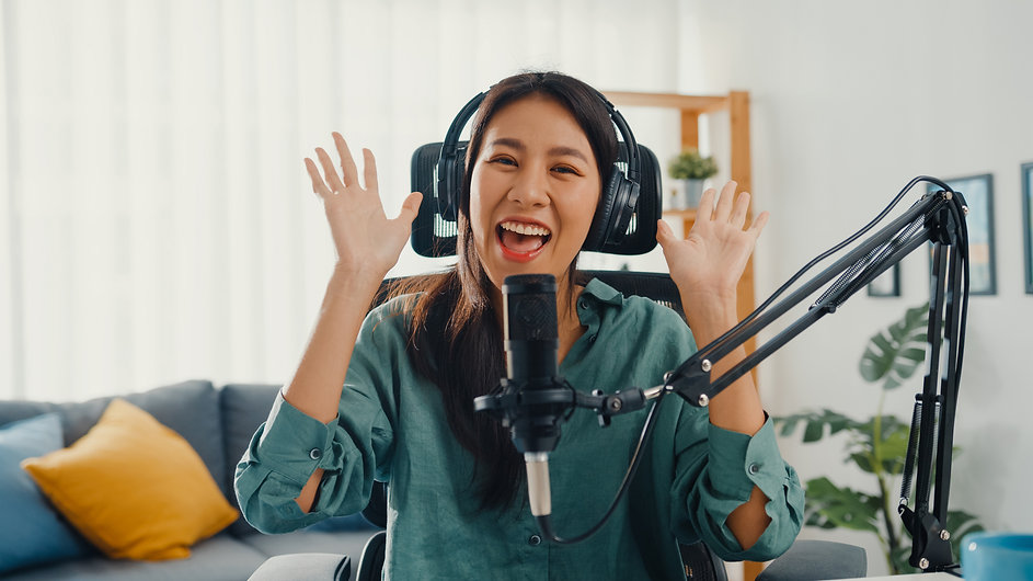 happy-asian-girl-recording-podcast-with-headphones-microphone.jpg