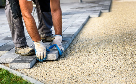 Laying gray concrete paving slabs in hou