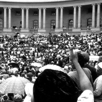 Black and white picture of thousands of women standing in front of Government buildings