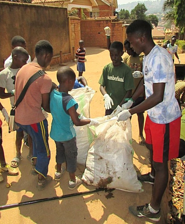 Local staff member, Mayele, picking up trash with participants