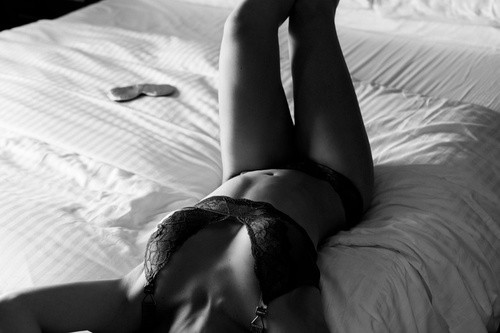 Confident woman in lingerie in bed