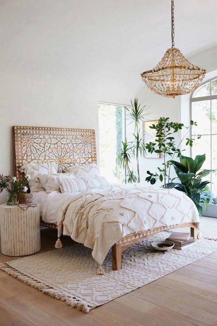 Rattan chandelier plants patterned rug hand carved wood headboard