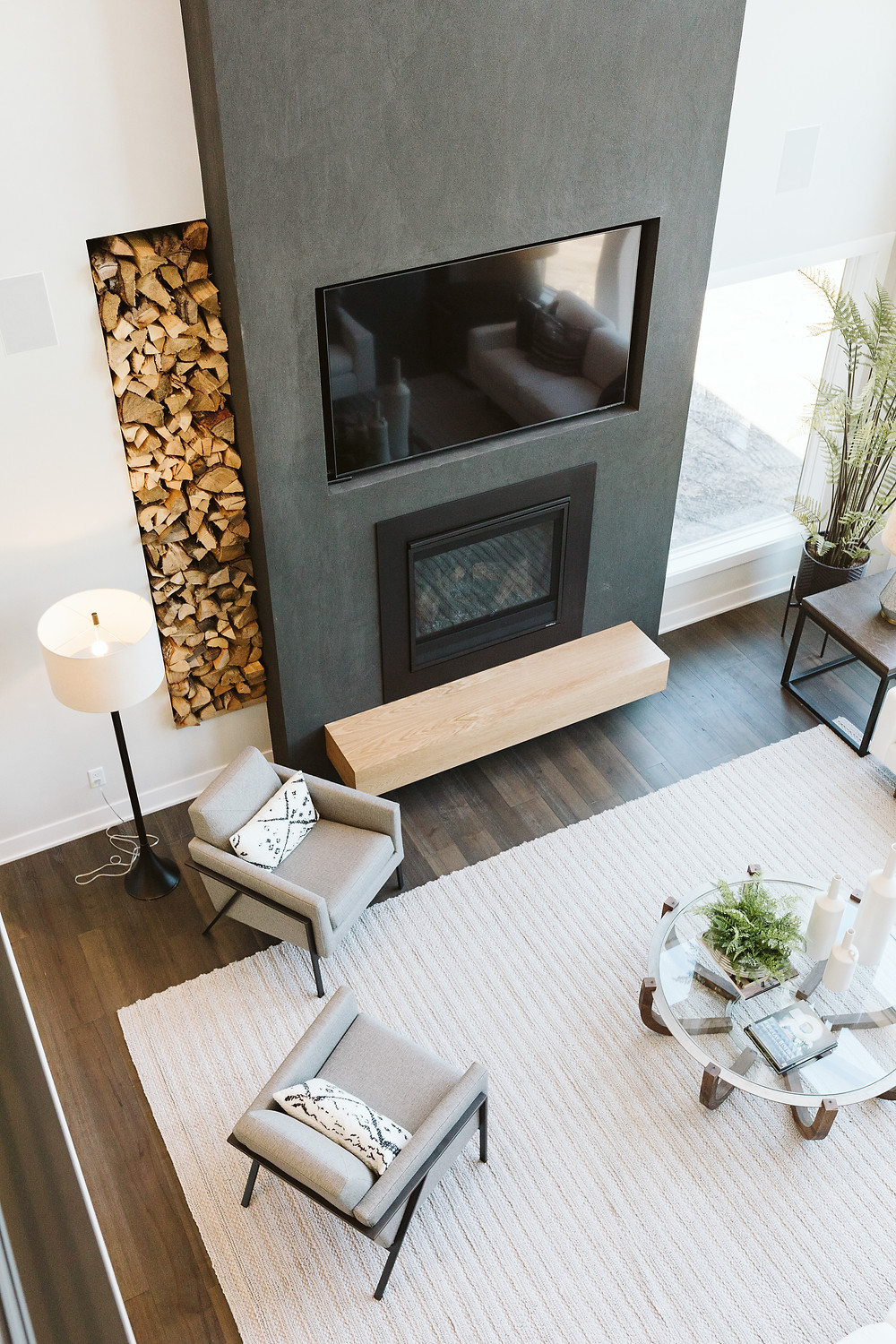 Black stucco fireplace, floating bench, stacked firewood