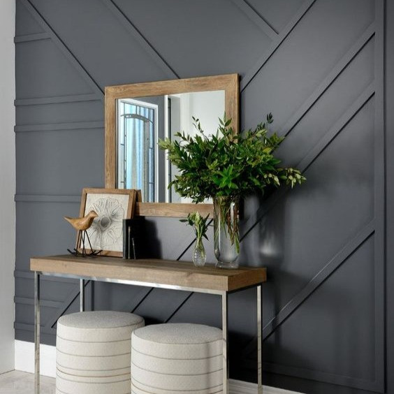 wood paneled wall mirror and table decor