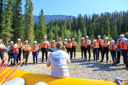 A raft guide sits on the side tube of a yellow, rubber raft that is on dry land. He is facing a crowd of customers who are watching him give a safety talk. The customers are in neoprene wetsuits and customer life jackets.
