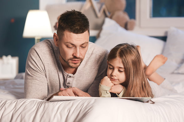 Father and his little daughter reading b