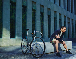 male model posing next to a bicycle