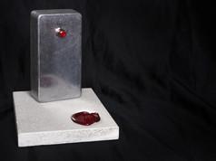 DESCRIZIONE Il pulsante fu l'innesco di una tragedia. Dalle successive indagini pare il disastro sia da imputare proprio ad un cattivo funzionamento del radiocomando.   DIMENSIONI 5.3.9 CM Base: 9.12.1 CM   MATERIALI alluminio, acciaio, plastica, componenti elettroniche Base: pietra
