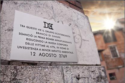 Targa 2, Anno 2769 - Roma (zona Trastevere)   TRA QUESTE VIE IL GRUPPO ECOTERRORISTA BRANCO DI SINOPE SGANCIÒ LA PRIMA BOMBA MINIATURIZZANTE RIDUCENDO LA MASSA CORPOREA DELLE VITTIME AL 47%, IN NOME DI UN'ESISTENZA A MINOR IMPATTO AMBIENTALE 12 AGOSTO 2769
