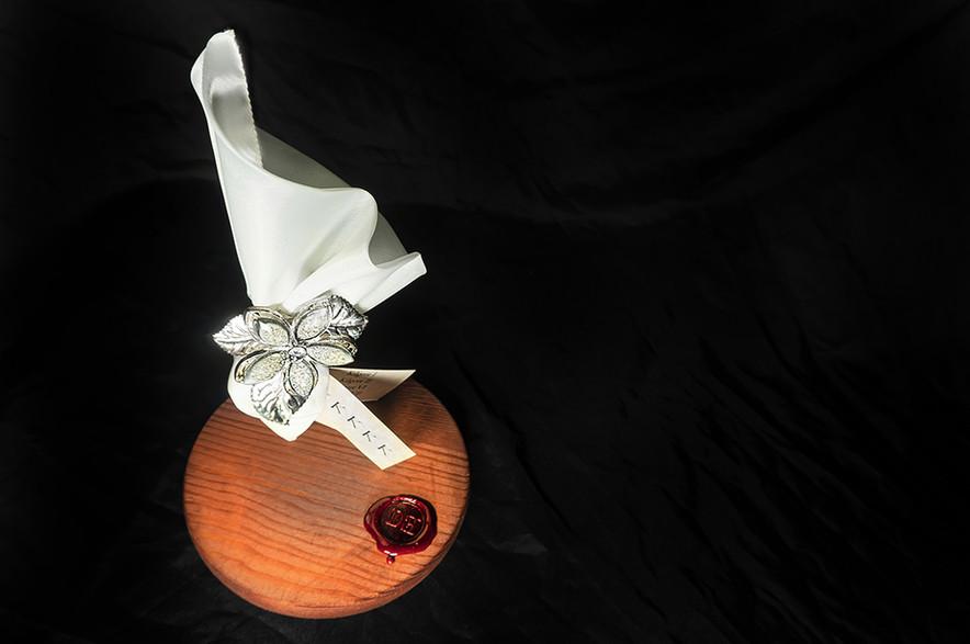 DESCRIZIONE Nonostante la singolarità dello sposalizio i cinque cloni optarono per una bomboniera tradizionale.   DIMENSIONI 9.17.3 CM Base: 12.12.1 CM   MATERIALI argento, pietra dura, tessuto, carta, confetti Base: legno, metallo