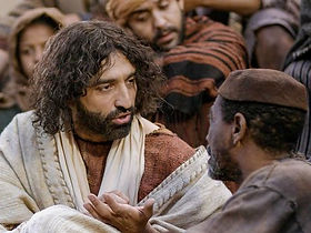 Jesus teaches a man seated in front of him at the Jerusalem temple.