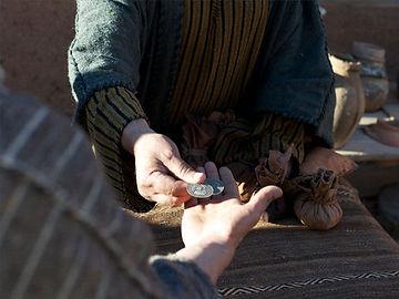 A merchant hands coins to a customer.