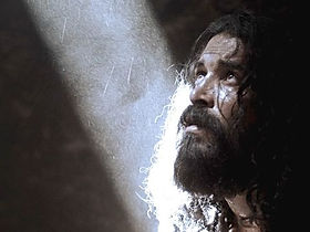 John the Baptist in prison. He looks up into a narrow beam of light shining into his cell.