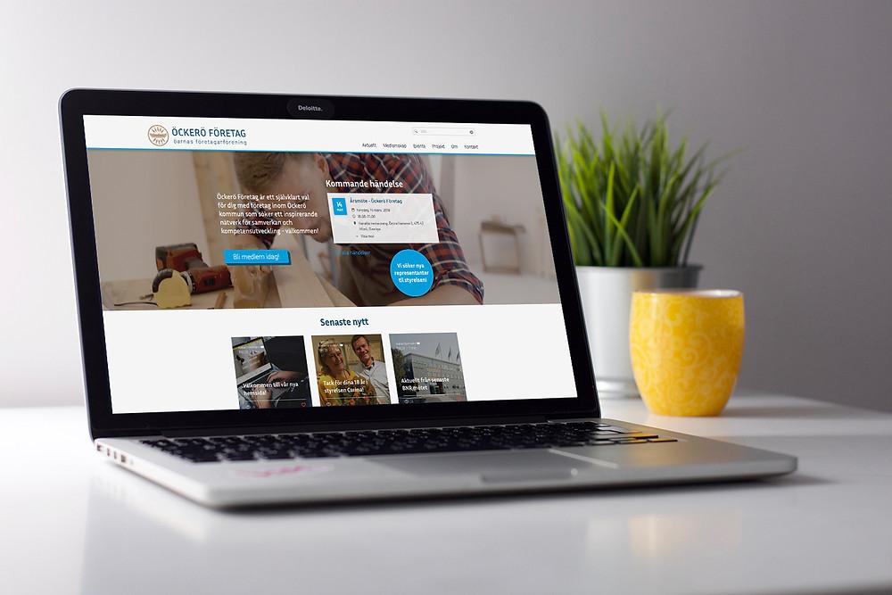 En person med dator i kneet där den nya hemsidan til Öckerö Företag visas på skärmen