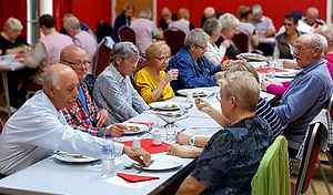 Many older people enjoying a lunch together, seated at long tables to talk with friends