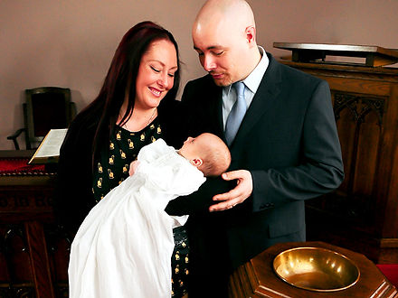A couple in church, admiring their young baby at a baptismal service