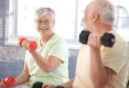Two older people exercising their arms by doing curls with light weights