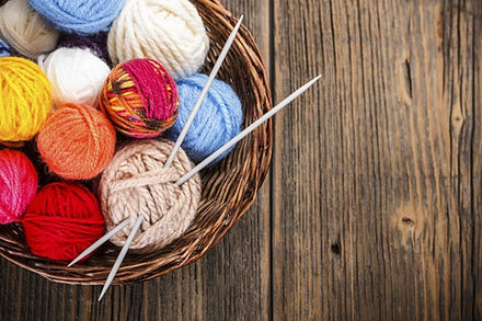 A collection of balls of wool in different colours with a pair of knitting needles