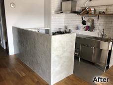 リフォーム後のキッチンの写真です。L字型の新しいカップボードを設置し、腰壁はWunderfixxで荒ら目の仕上げとしています。
