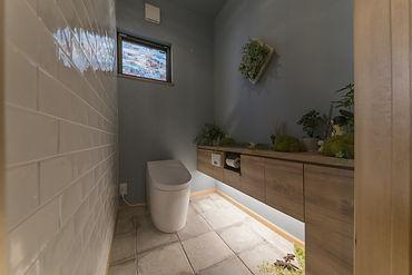 リノベーション後のトイレの写真です。既存のトイレスペースより幅を広げたことでトイレ内に収納棚を設置できました。